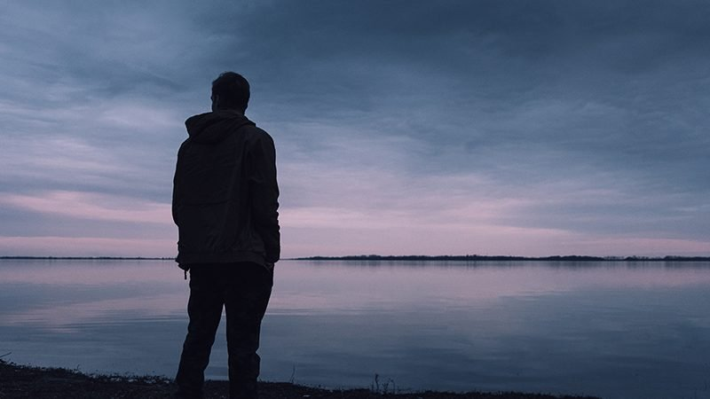 Man standing by a lake | men's mental health